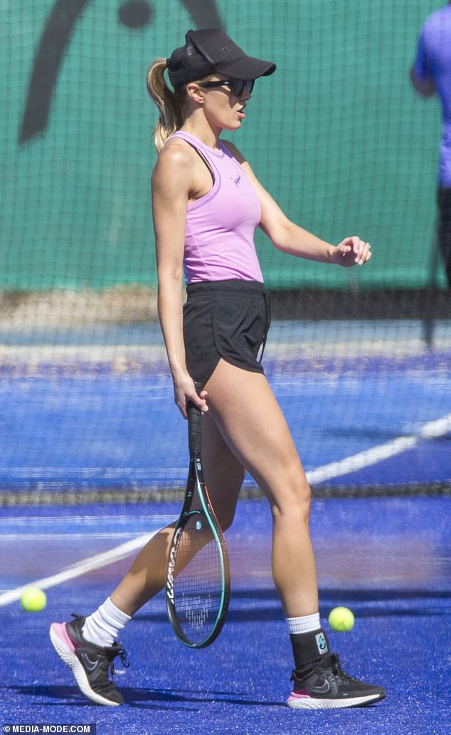WAG Rebecca Judd flaunts her toned frame as she enjoys a game of tennis in Melbourne