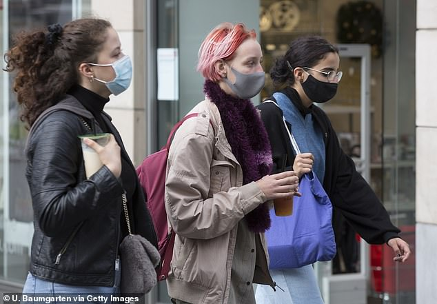 Near-universal mask wearing would eliminate the need for new lockdowns, the WHO's Europe director said today (pictured, people wearing masks in Bonn, Germany)