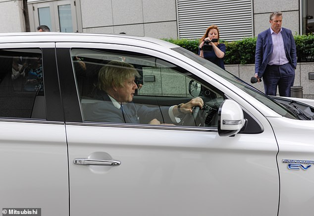 Boris Johnson pictured in 2015, when the PM was mayor of London, driving the just-released Mitsubishi Outlander Plug-in Hybrid SUV at its official launch in Tokyo