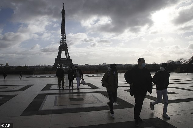 People wearing face masks in Paris cross thethe Trocadero square, near the Eiffel Tower on November 19.Europe has registered more than 29,000 virus deaths in the last week alone and much of the continent is now living under similar measures as in March and April