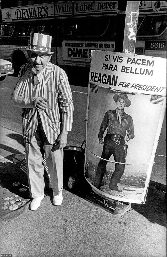 Though not intentional, often the advertisements and posters in the framing in the Godlis images provide a time stamp of the era. The above image depicts a man dressed as Uncle Sam while campaigning for Ronald Reagan in 1980, the sign written in Spanish translates to: 'If you want peace, prepare for war'