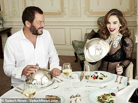 Loving it: Lily smiled at the camera as Dominic watched her unveil her meal