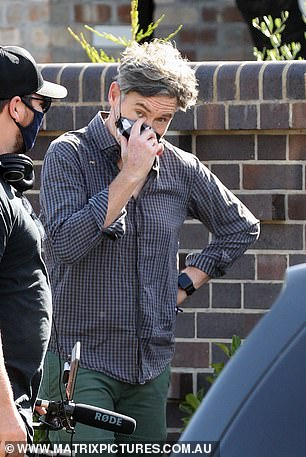 Casual: He completed the look with a watch as he carried a pair of glasses and kept his silver locks scruffy