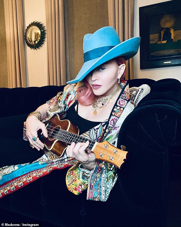 In the stunning post: Her Madgesty sat on a couch in a lovely multicolored caftan whilst playing a small ukulele