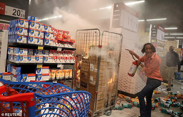 A woman puts out a fire at a vandalized Carrefour store during a march in Sao Paulo on National Black Consciousness Day and in protest against the death of Freitas