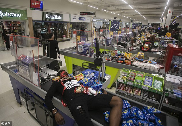 Jonata Anjo lies on a checkout counter at a Carrefour supermarket during a protest against the murder of Black man Joao Alberto Silveira Freitas at a Carrefour supermarket the night before