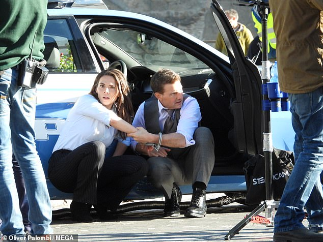 Back to work: Tom Cruise and co-star Hayley Atwell were handcuffed together as they filmed intense scenes for Mission Impossible 7 in Rome on Saturday