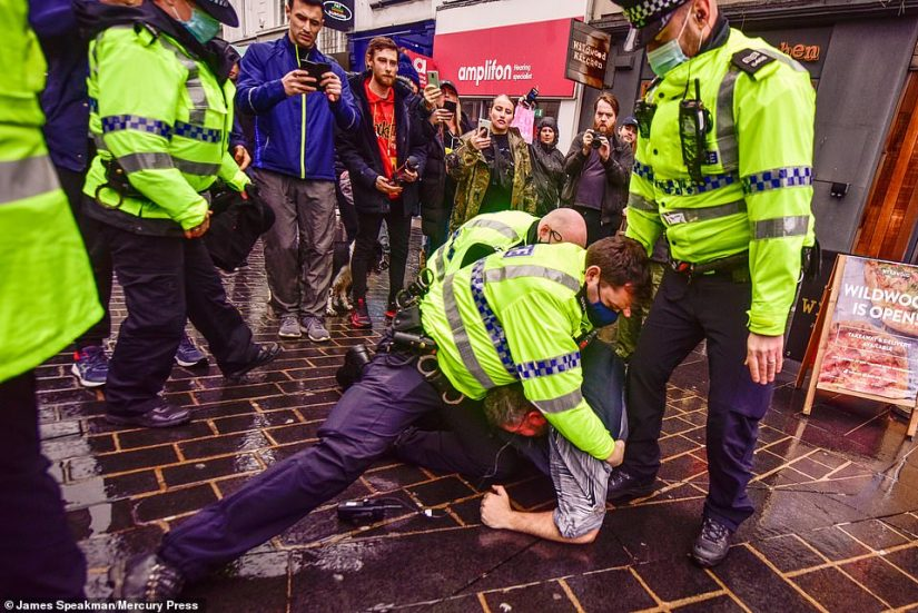 Police grapple with a protester on the ground as crowds of others watch on during a day of demonstrations in Liverpool