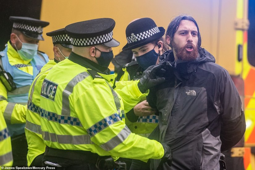 A man is restrained by police officers during the rally in which people marched through Liverpool shouting 'freedom'