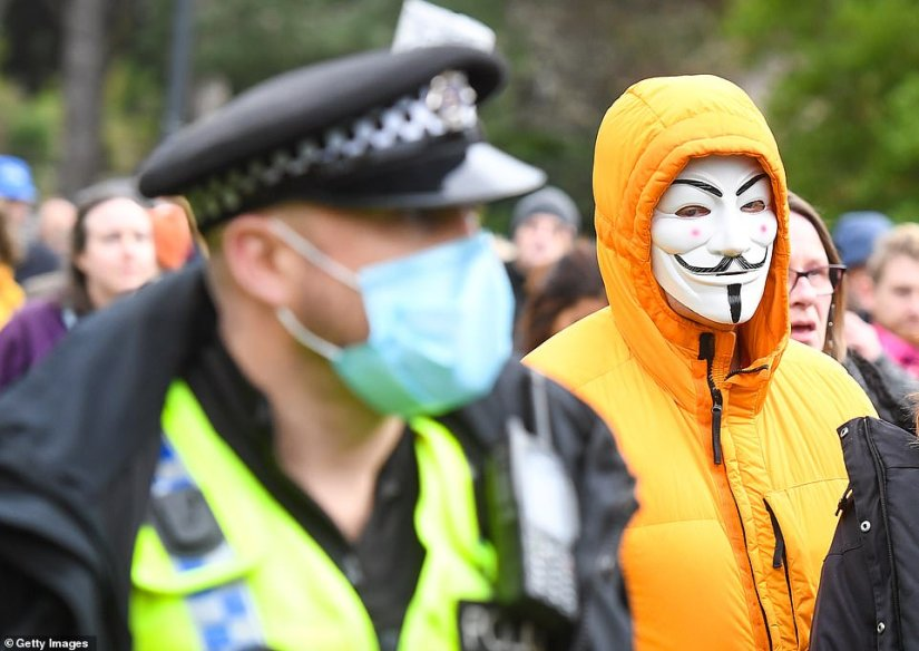An anti-lockdown protester is seen in a Guy Fawkes mask as the march in Bournemouth heads through the town centre