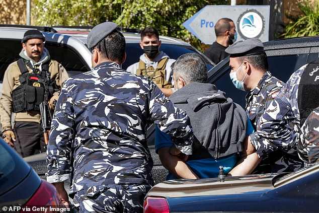 The police in Beirut confirmed 15 inmates has been re-arrested so far and four had handed themselves in. Pictured: Police escort a prisoner who had fled a detention centre