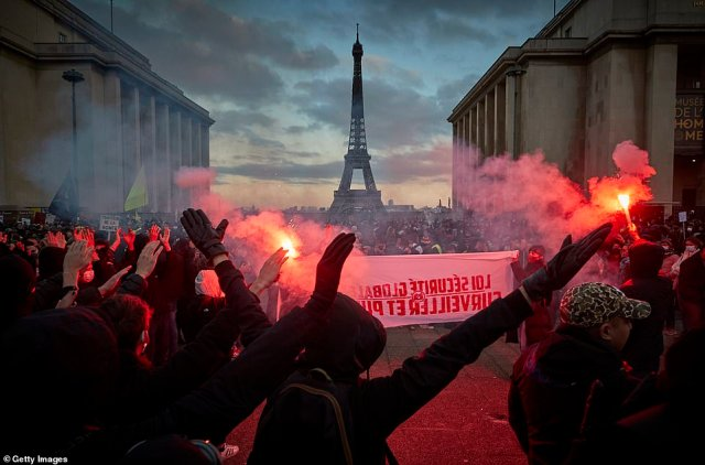 Demonstrators at Place duTrocadero light flares as they demonstrate against a proposedsecurity law which civil liberties campaigners say would impinge on freedom of information and media rights