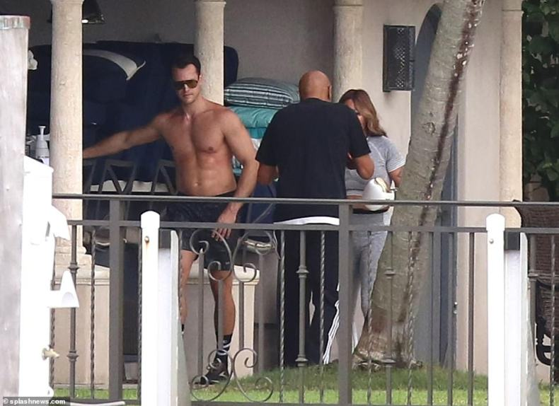 Pictured: a shirtless Thomas Bates (left) walks by Orianne Cevey and her personal trainer on Friday amid the couple's contentious legal battle over the home with Phil Collins