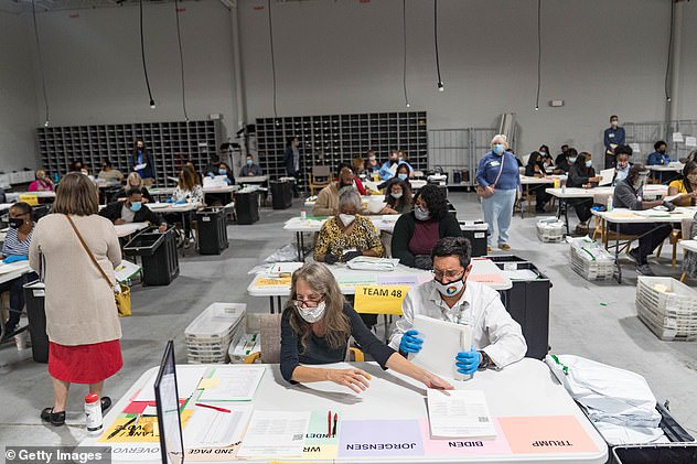 Georgia election workers handle ballots as part of the recount this week
