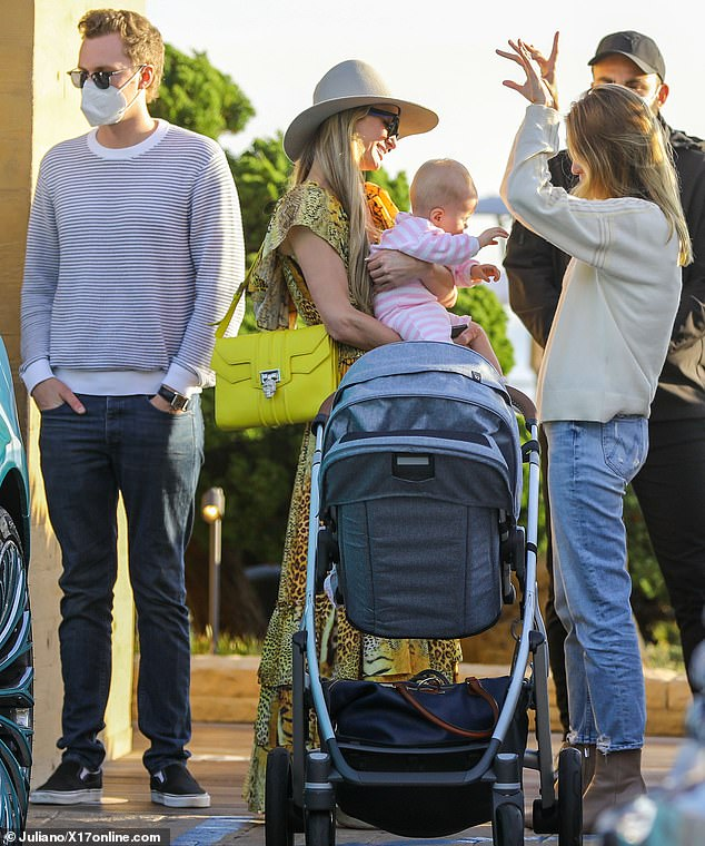 Proud aunt: She carried a yellow leather handbag over her shoulder with a jeweled skull buckle, as she waited at the valet stand with baby Milou in her arms