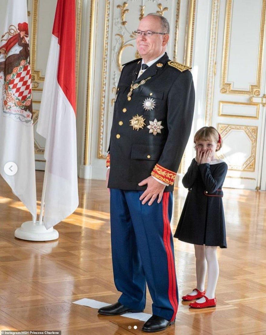 На втором снимке принцесса Габриэлла, одетая в лакированные красные туфли и темно-синее плиссированное платье с белым воротником, стояла позади своего отца, прижав руки к лицу, когда ее отец позировал для фотографий.