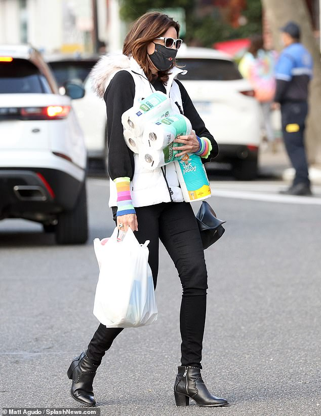 Laidback look: Stepping out in an all black ensemble, she layered up in a white fur trimmed vest