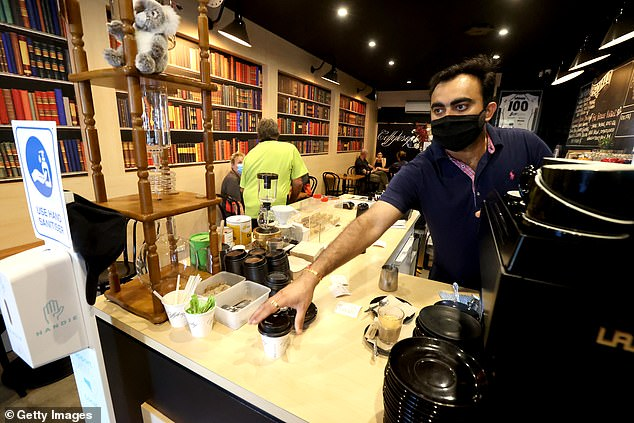Barista Harsh Mehta serves coffee to customers at his Coffylosophy cafe in Adelaide after lockdown restrictions were lifted on Sunday