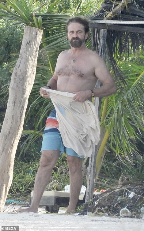 Shirtless Gerard Butler, 51, enjoys a chat and a dip in the ocean with a bikini-clad beauty