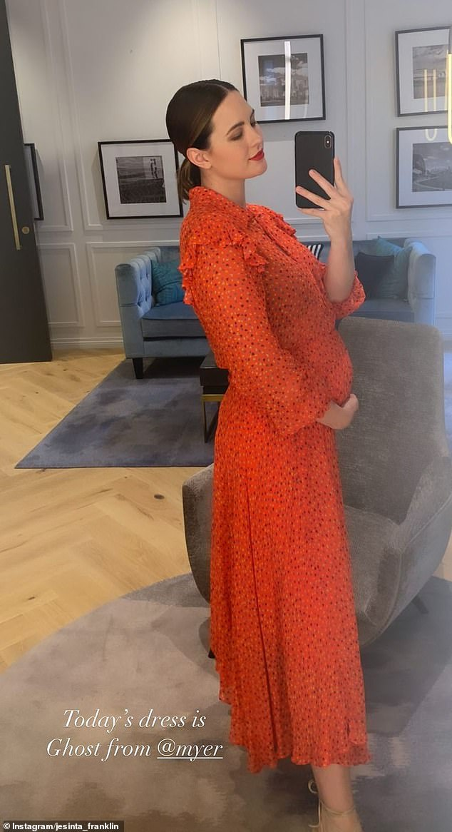 Pregnant WAG Jesinta Franklin exudes glamour in orange frock as she cradles her growing baby bump