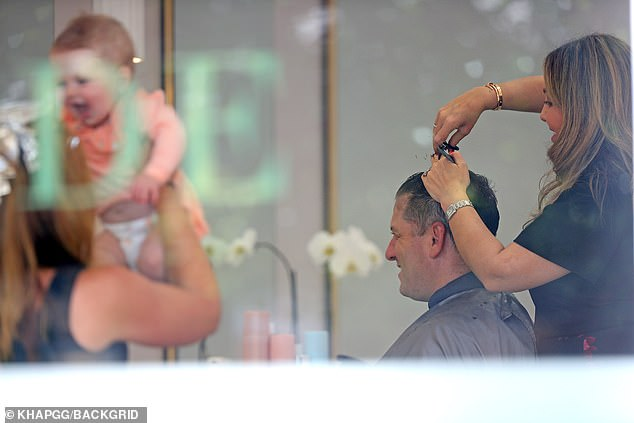 Baby on board: They briefly stopped by the hair salon, and another patron offered to hold a smiling Harper as her dad got a trim nearby