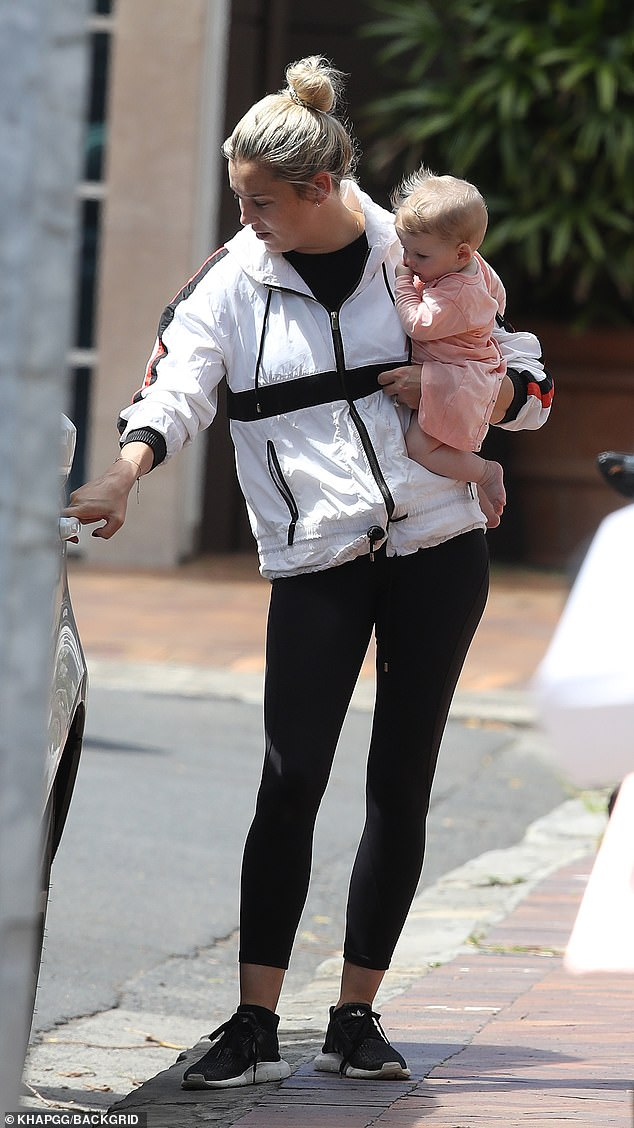 Sporty style: Jasmine opted for black workout leggings, which she paired with a matching T-shirt worn under a white anorak