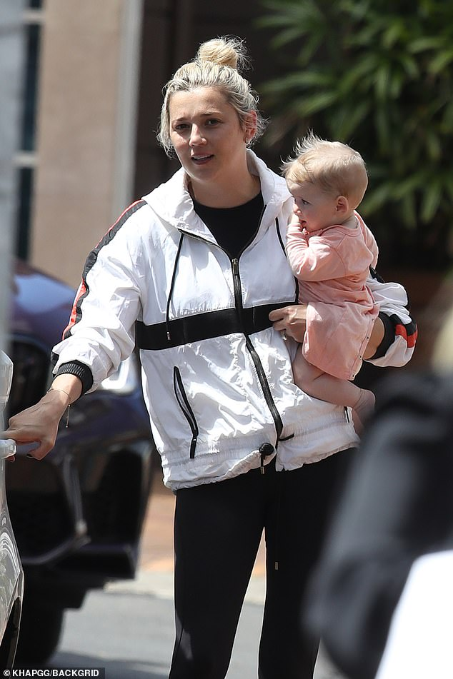 Mum on duty: As Karl got his hair done, Jasmine looked after their baby daughter, Harper