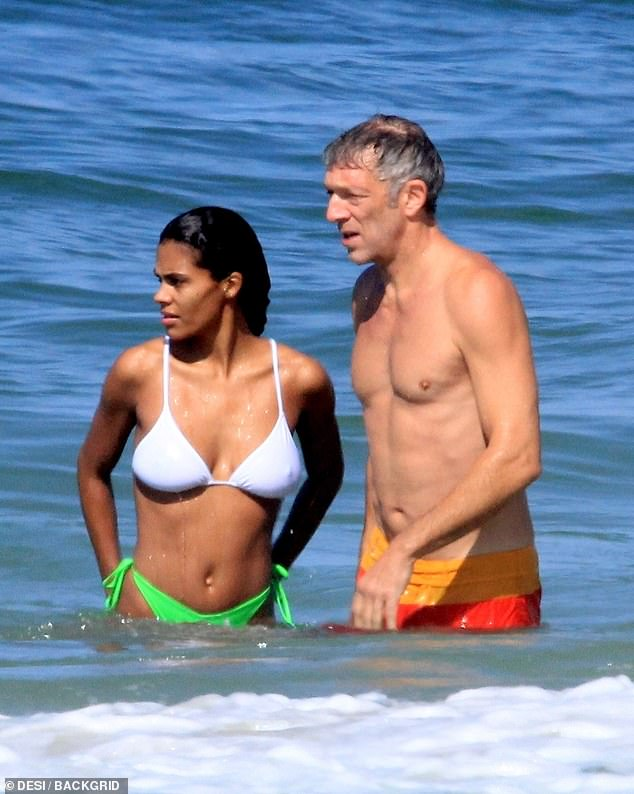 Still got it: Her much older man, meanwhile, showed off his trim and youthful physique by swimming in just a pair of orange and red board shorts