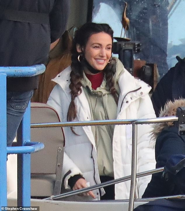 Casual:The actress, 33, donned a white padded coat as she was joined by members of the cast and crew on a boat for the shoot