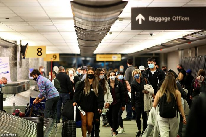 DENVER, COLORADO:Despite the devastating figures and the fact that hospitals are already overwhelmed in parts of the country, the death toll is only expected to surge with millions defying official warnings and traveling for Thursday's Thanksgiving holiday. Travelers collect their luggage at Denver airport yesterday
