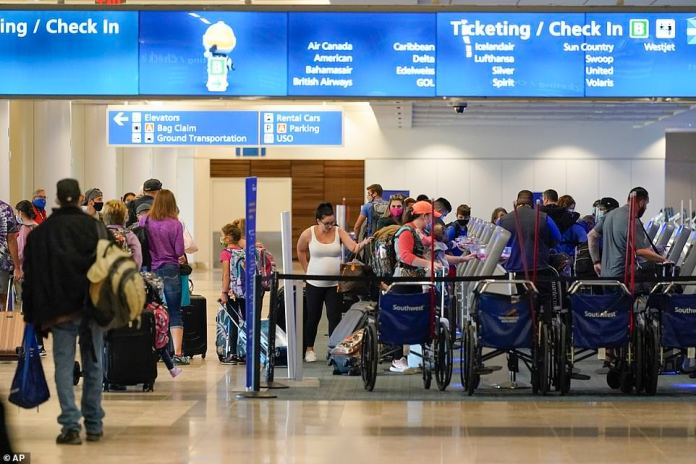 ORLANDO, FLORIDA:Holiday travelers check in at kiosks near an airline counter at Orlando International Airport yesterday
