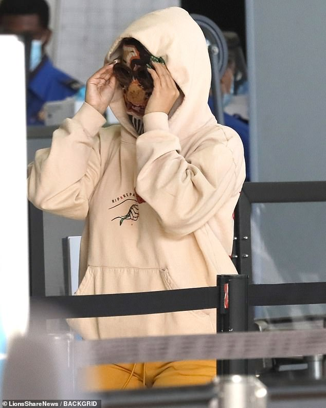 Privacy please:The hitmaker pulled a butter yellow Rip N Repair hoodie over her head, giving the look another level of privacy