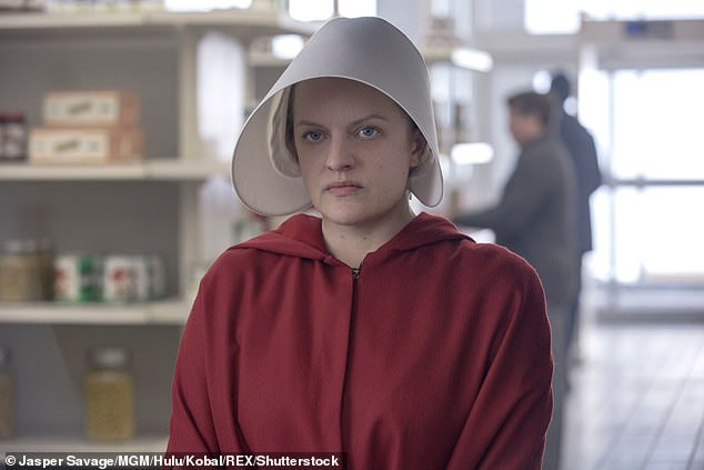 Margaret's dystopian novel details a dystopian society in the near future in which fertile women, known as handmaids, are forced to provide children for the rich and influential. Pictured,Elisabeth Moss in the TV adaptation of the book