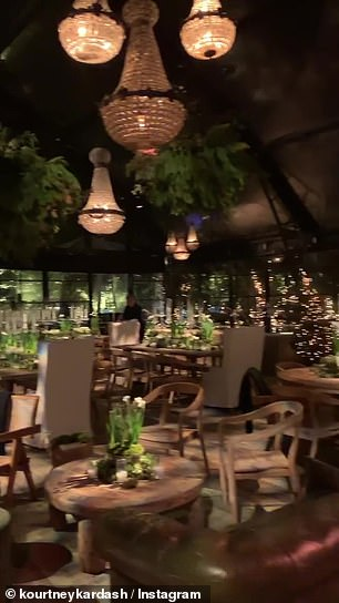 Inside, Kourtney had a dim lit set up featuring wooden tables and matching chairs