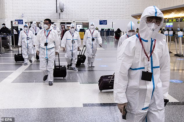 Airline crew members wear full hazmat suits as they arrive at LAX on Tuesday