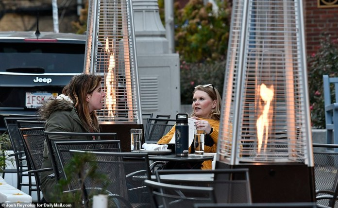 BOSTON: Two women look over a menu between space heaters in a parking lot-turned-dining area