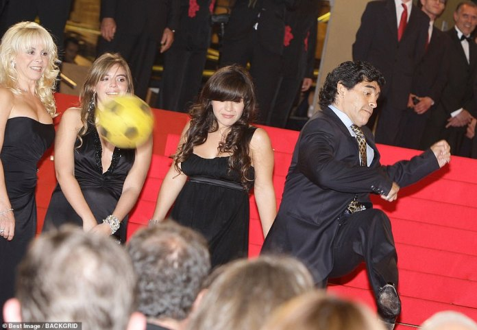 Maradona boots a football while attending a red carpet event with his wife Claudia (left) and daughtersDalma and Ganina