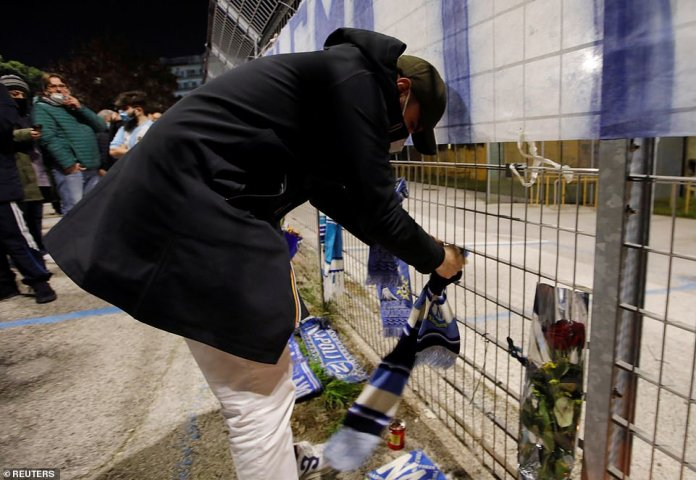 A man hangs a Napoli scarf on a fence as people gather to mourn the death of Argentine soccer legend Diego Maradona outside San Paolo stadium in Naples, Italy, November 25, 2020