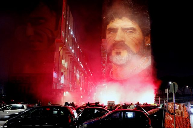 People light flares as they gather under a mural depicting soccer legend Diego Maradona, in Naples, Italy, Wednesday, Nov. 25, 2020