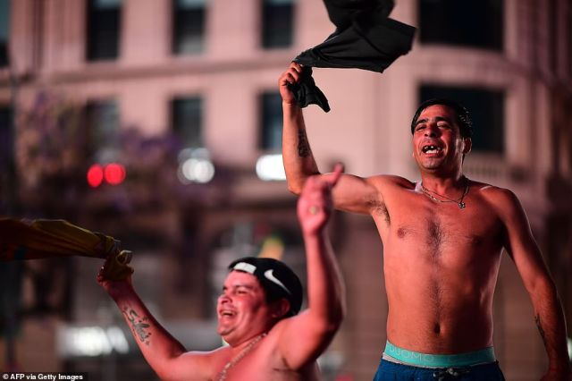 Fans wave their shirts in tribute to Maradona last night as they gathered by the Obelisk in the Argentinian capital