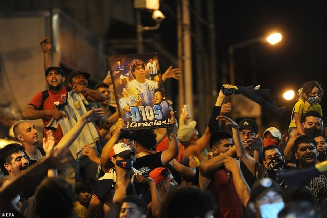 Mourners outside the morgue in Buenos Aires hold up football shirts and pictures of Maradona, with a placard incorporating his number 10 shirt into the word Dios, Spanish for God