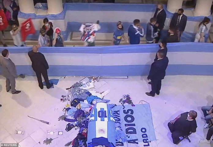 Public procession: Flags, flowers and football shirts are thrown at the foot of Maradona's casket today as thousands of mourners file past the coffin to play their last respects to Argentina's greatest football hero