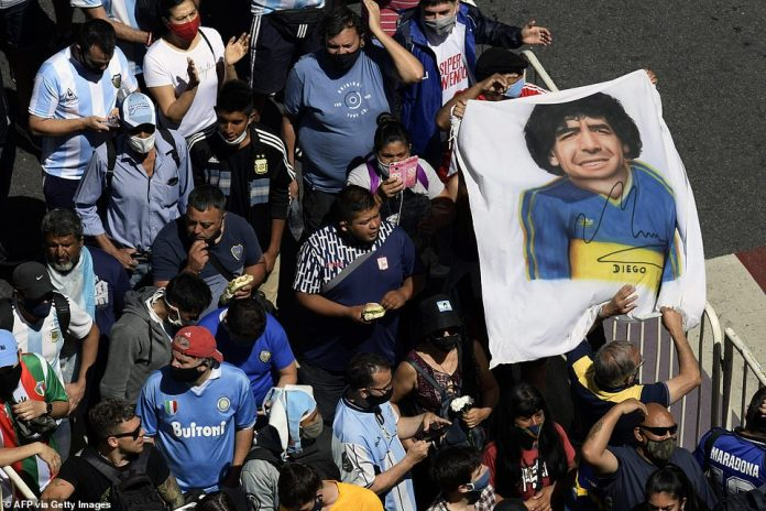 A banner of Maradona's face in the colours of his former club side Boca Juniors is carried along the queue outside the Casa Rosada in Buenos Aires today