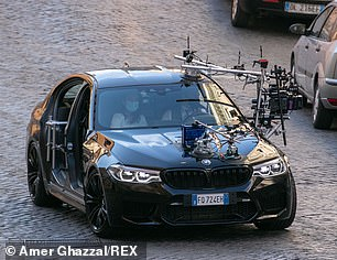 Off they go: The duo were seen riding around in the black car amid filming for the latest Mission Impossible film