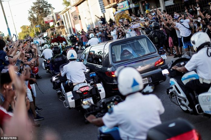 People react on the street as the hearse carrying the casket of soccer legend Diego Armando Maradona travels to Bella Vista cemetery, on the outskirts of Buenos Aires, Argentina