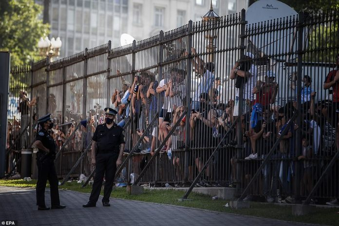 Supporters of Diego Armando Maradona clamber up the fence surrounding the precinct of the presidential palace on Thursday