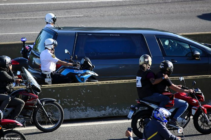 The hearse carrying the body of Diego Maradona travels along the highway