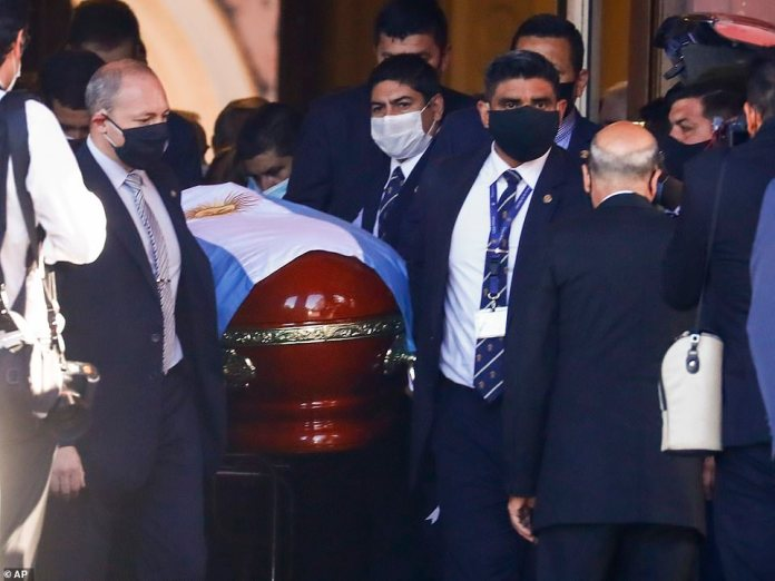 Maradona's coffin draped in the Argentinian flag is carried out of the presidential palace late on Thursday afternoon