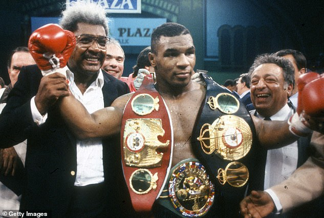 Tyson celebrates beating Carl Williams to claim the WBA, WBC and IBF titles in 1989