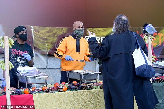 Common people: Her John Wick 2 star boyfriend meanwhile served free meals while wearing an orange sweater